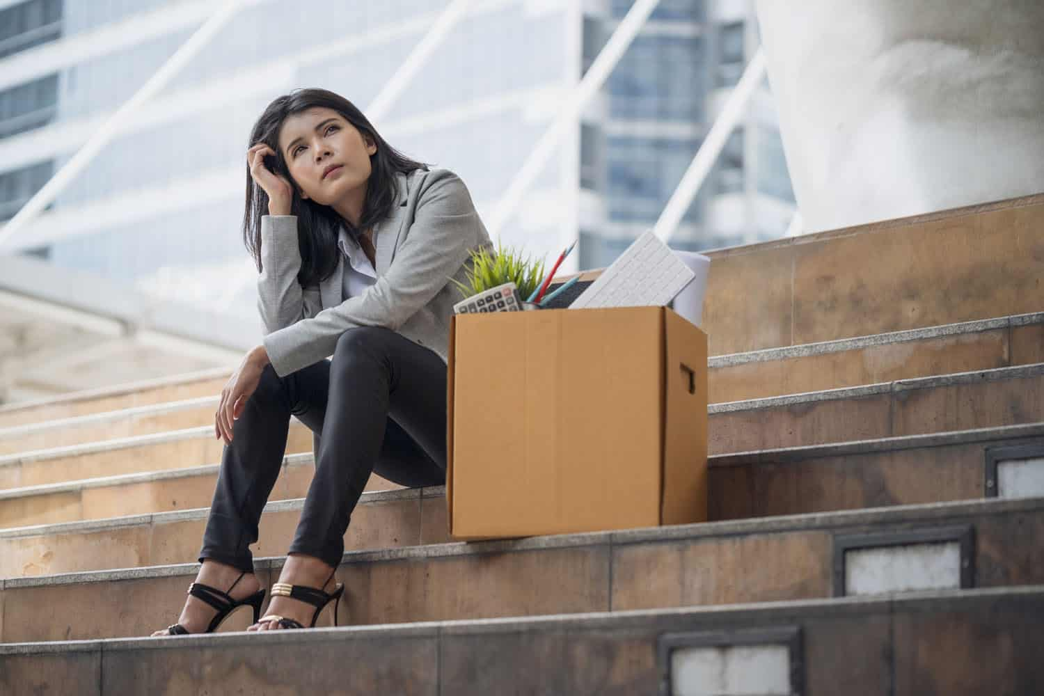 woman sitting on stairs with box after losing her job