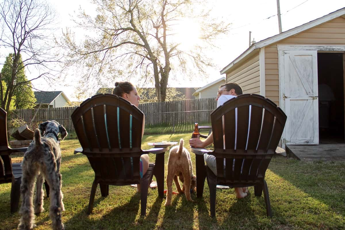 couple sitting outside with dogs