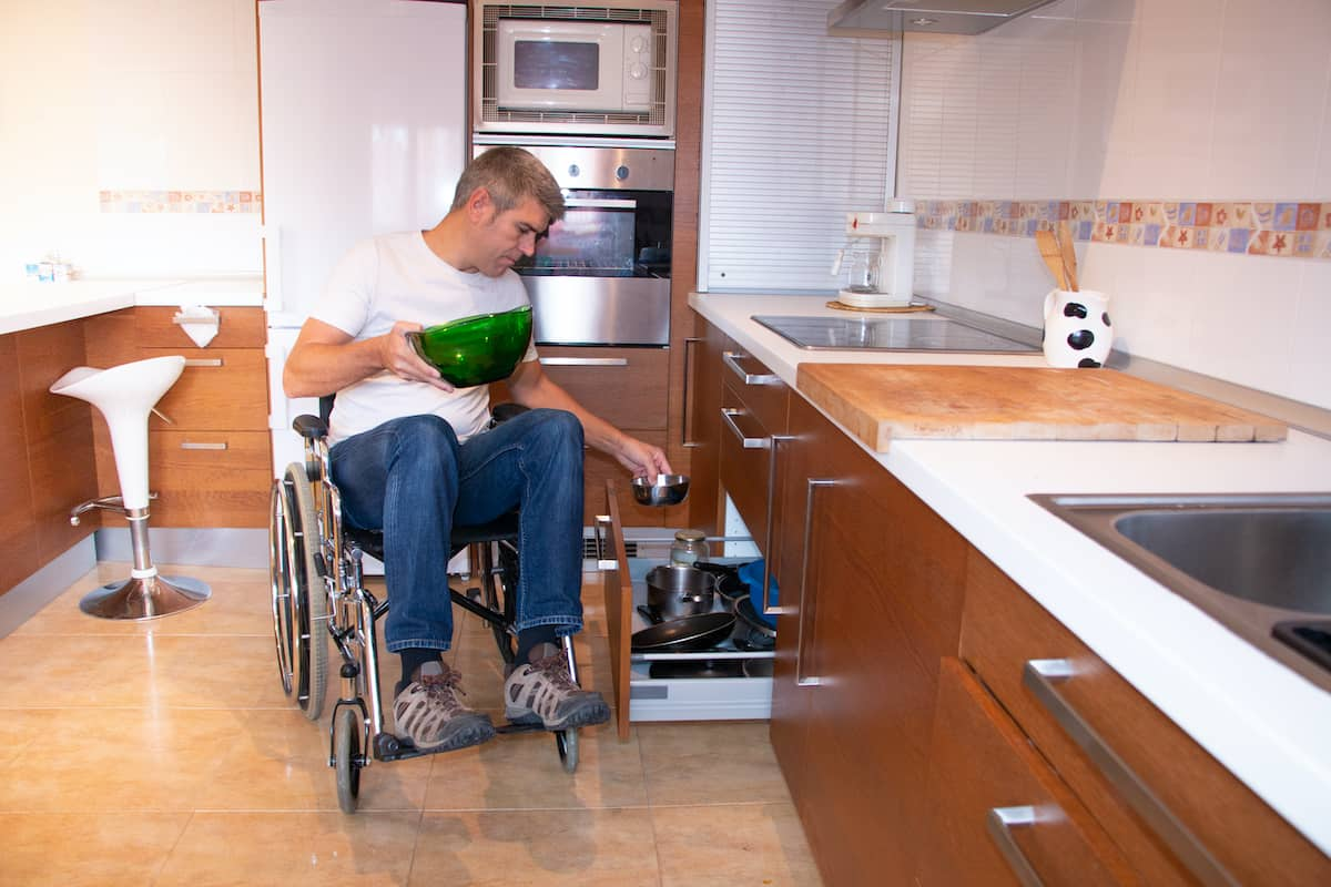 A man in a wheelchair in a handicapped-accessible apartment putting away dishes.