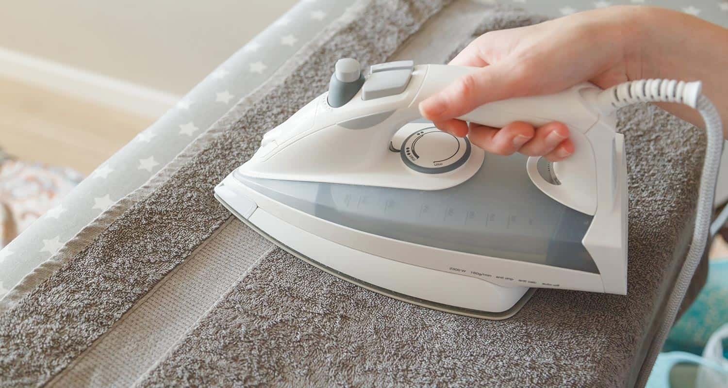 Person drying clothes by ironing with a towel
