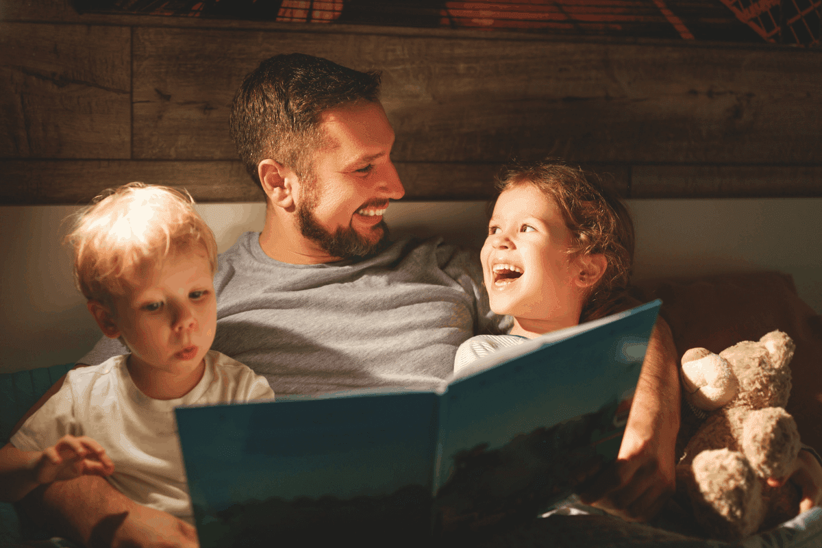 Two children, a boy and a girl, sit with their dad as they read a bedtime story.