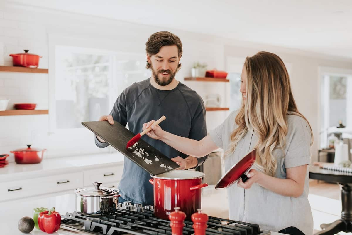 A man and a woman cooking together in a kitchen.