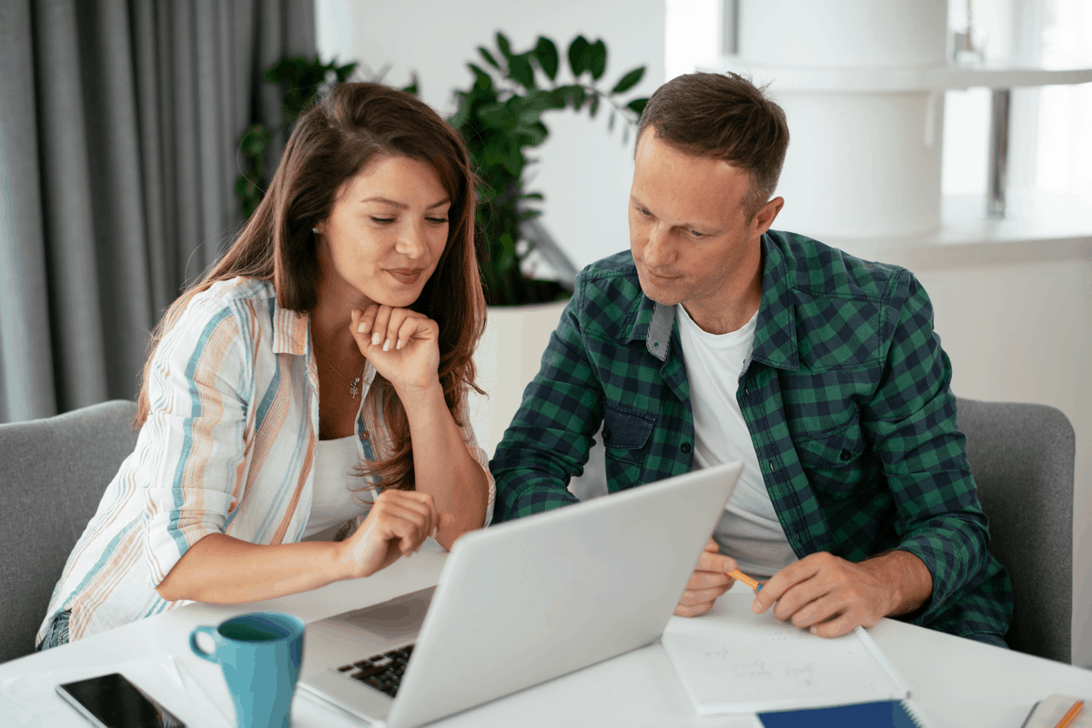 A couple at a laptop reviewing documents and looking for no credit check apartments