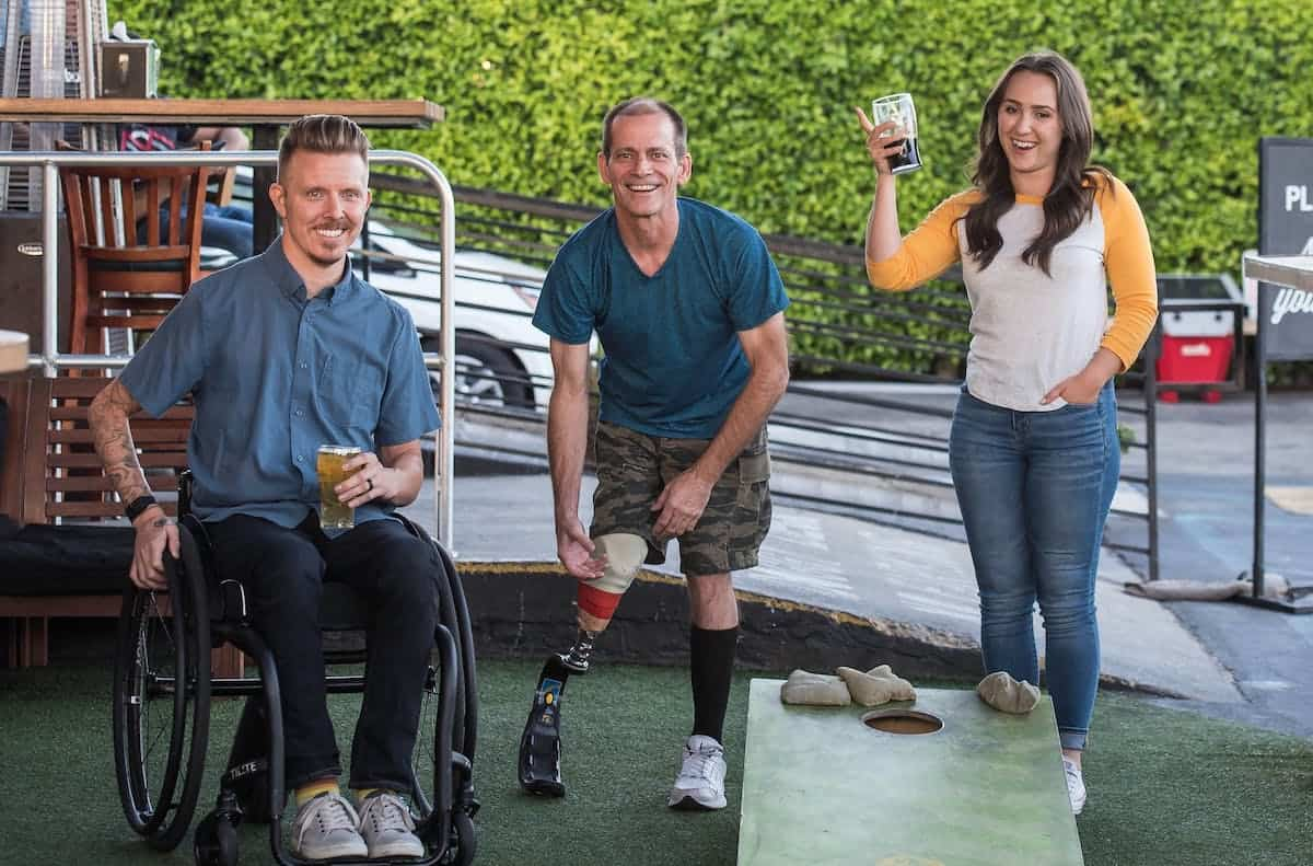 Three smiling people outdoors with beers: one man in a wheelchair, one man with artificial lower right leg; one woman standing and raising a glass at handicap-accessible apartment