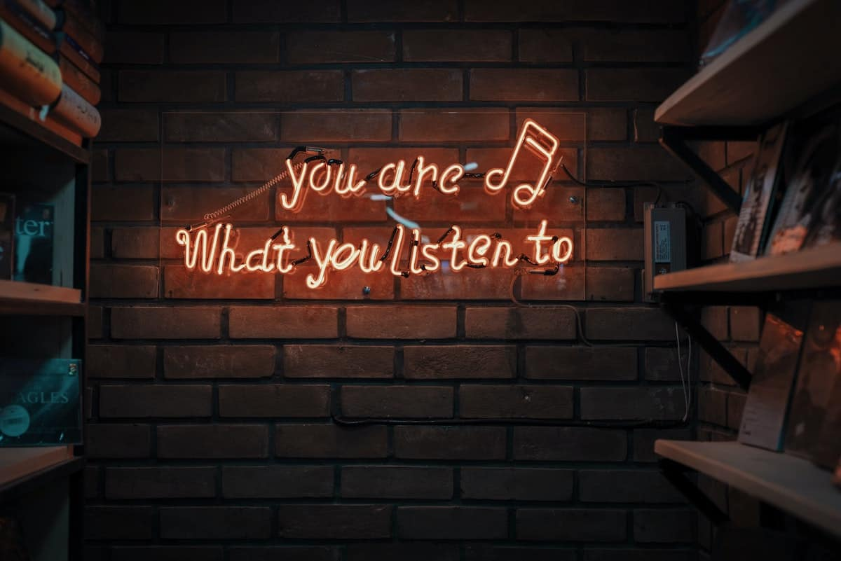 A red neon sign that says you are what you listen to on a brick wall.