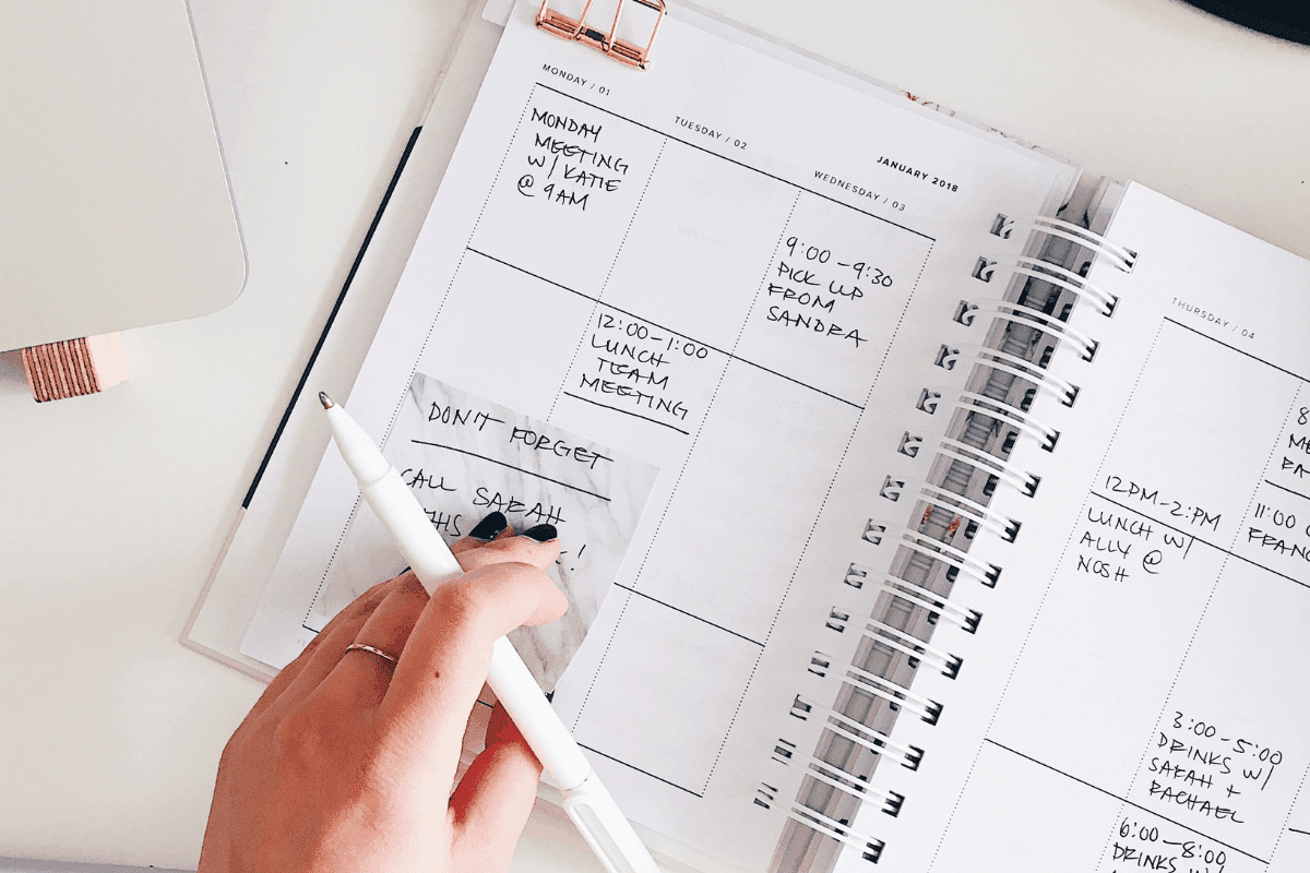 A woman writing in her planner, her routine and plans.