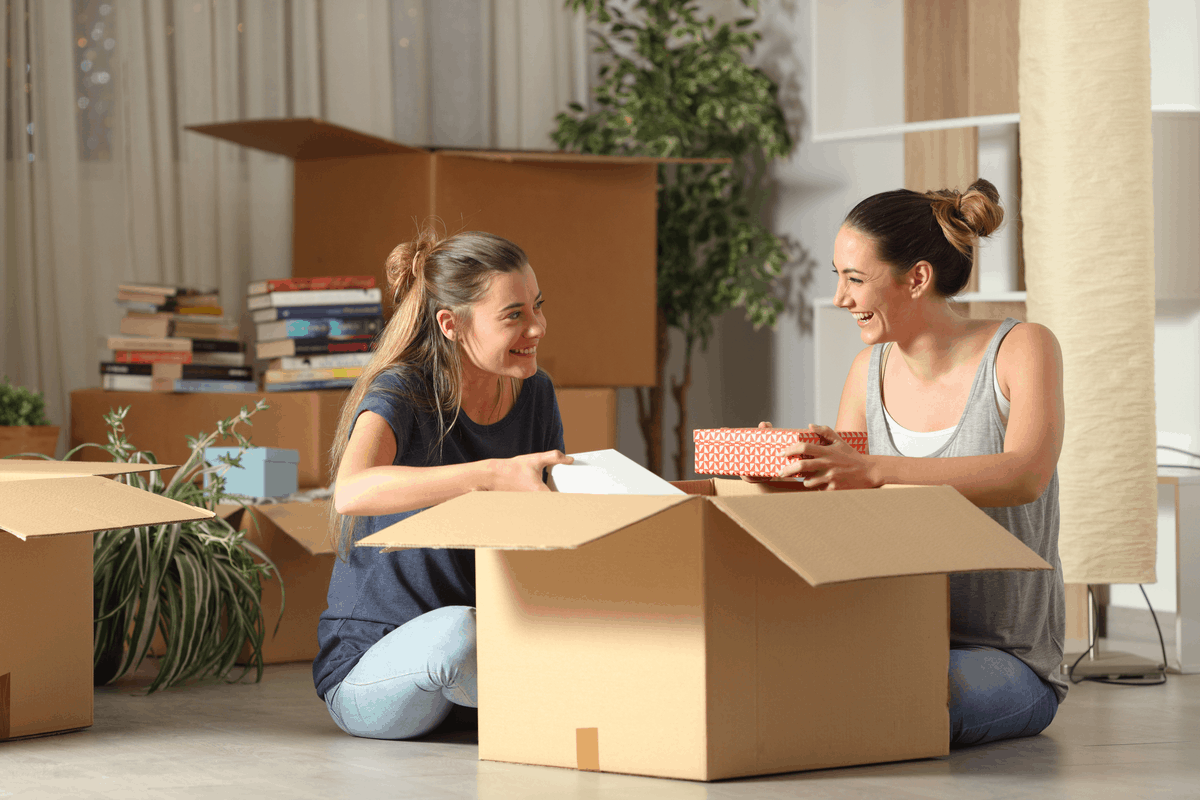 Two women unpacking a box in an apartment.