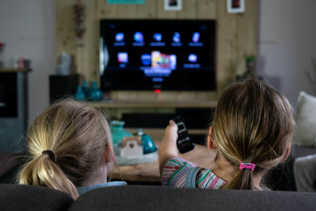 Two children on a couch holding a remote to a Smart TV.
