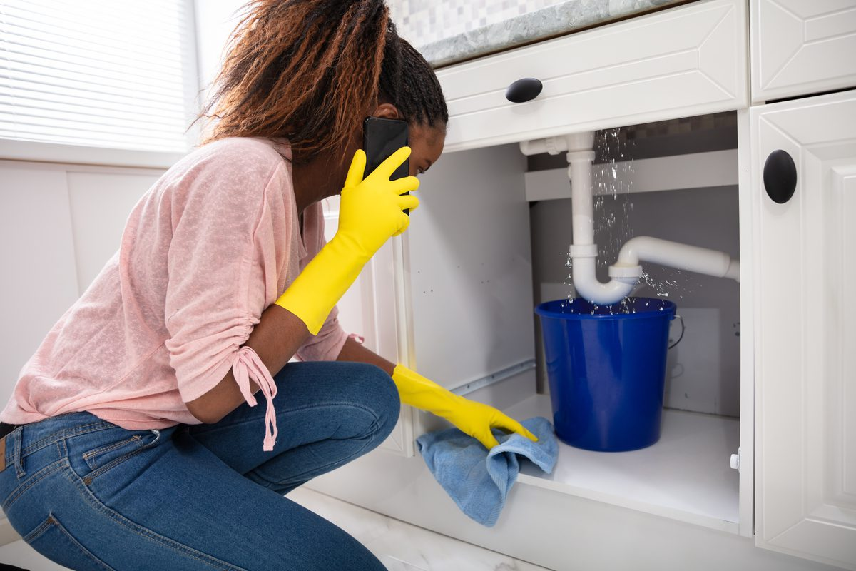 Woman on the phone with landlord because her sink is leaking.