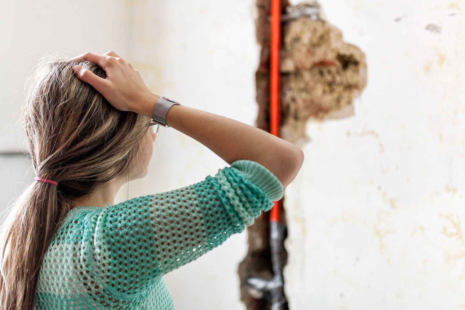 Woman concerned and looking at mold from water damage
